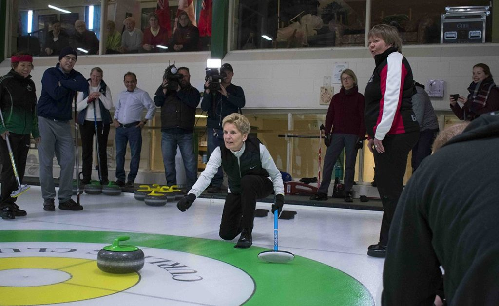 Ontario Premier Kathleen Wynne tossing a curling rock on the rink at the Leaside Curling Club.