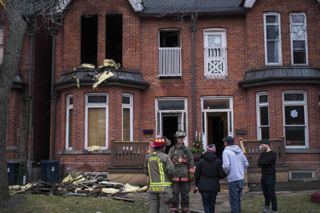 TORONTO, ON – 12/20/17: The homeowner of 66 Stafford St. ran into the house to save her family photos after firefighters beat the blaze. Unfortunately, this fire, five days before Christmas, was not her first. Last year, she had another house fire on the same street. She bought the firefighters coffee as a token of gratitude.