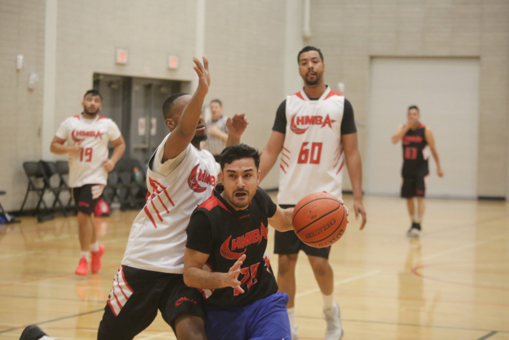 A basketball player races toward the net with opponents closing in